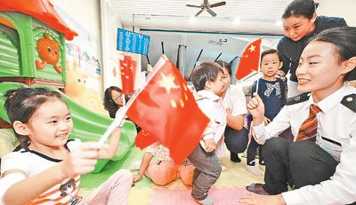 国庆我坚守:北京南站润秋爱心服务区的工作人员正在儿童乐园陪伴小朋友等候上车