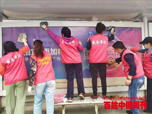 山东烟台:雷锋志愿者对海港路公交站点进行卫生清理